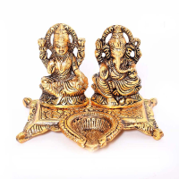 Goddess Laxmi and Lord Ganesha figurine with diya